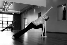 hot Yoga studio practice room with woman striking yoga posing